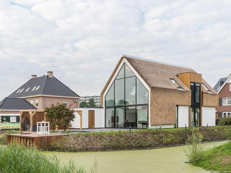 Moderne villa met gestucte gevels en rieten kap